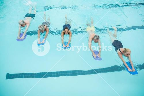 Senior swimmers and trainer swimming with kickboards in pool