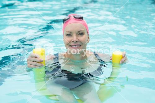 Mature woman swimming with pool noodle