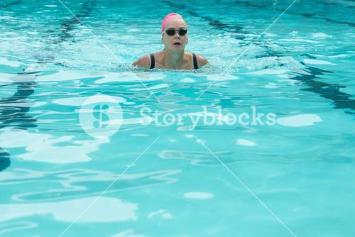 Woman wearing goggles while swimming in pool
