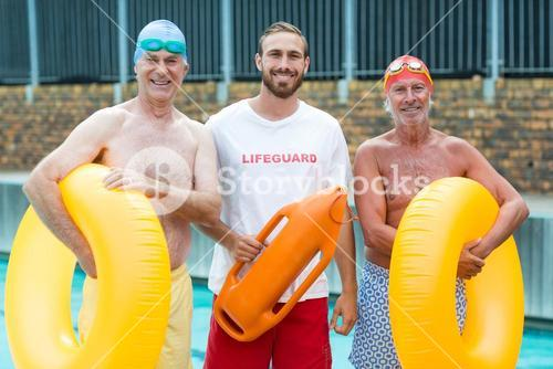 Lifeguard with senior swimmers at poolside