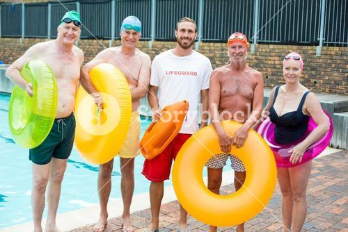 Male lifeguard with senior swimmers standing at poolside