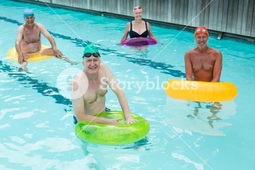 Seniors swimming with inflatable rings in pool