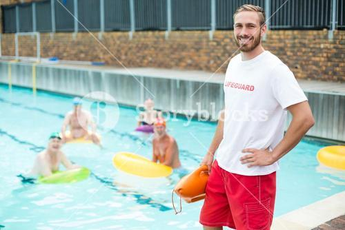 Male lifeguard standing while swimmers swimming in pool