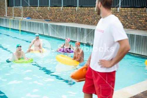 Lifeguard looking at swimmers swimming in pool