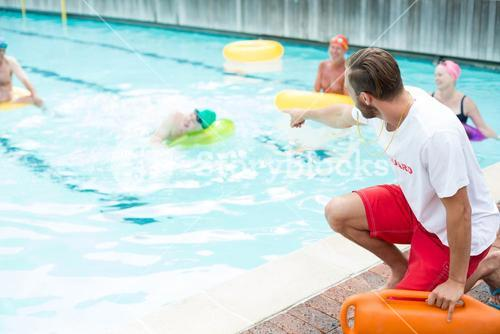 lifeguard assisting swimmers at poolside