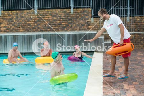 Lifeguard helping swimmers at poolside