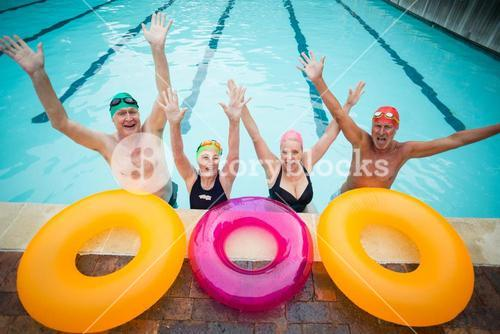 Cheerful senior swimmers with inflatable rings at poolside