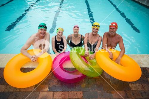 Senior swimmers with inflatable rings standing at poolside