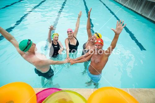 Active seniors stacking hands in pool