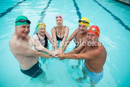 Cheerful senior swimmer stacking hands in pool