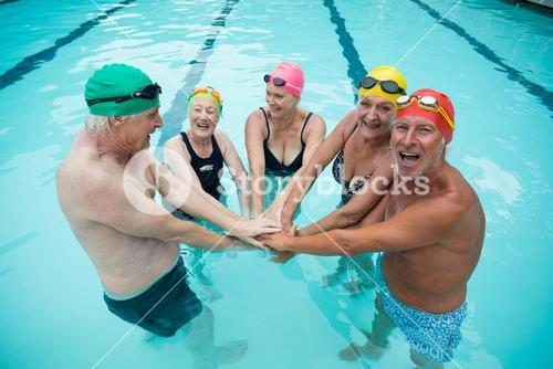 Happy senior swimmer stacking hands in pool