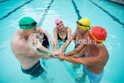 Swimmers stacking hands in pool
