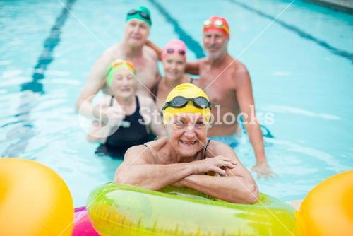 Senior woman by inflatable rings with friends