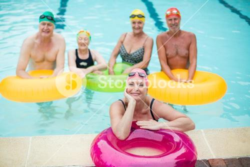 Swimmers with inflatable rings in pool