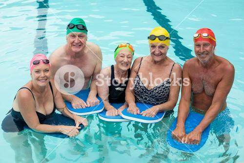 Senior swimmers posing with kickboards in pool