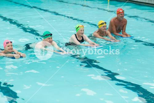 Swimmers with kickboards swimming in pool
