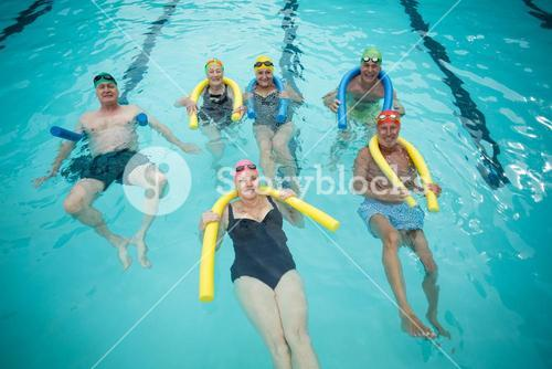 Swimmers swimming with pool noodles