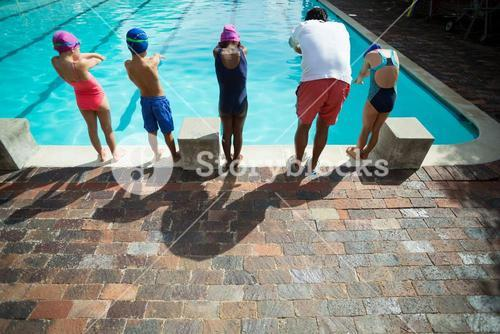 Male instructor with children at poolside