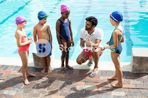 Instructor training children at poolside