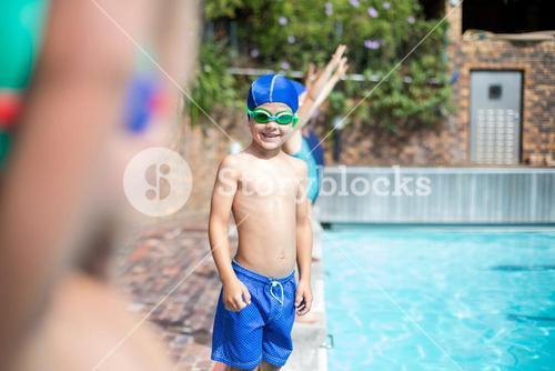 Little boy wearing swimming goggle at poolside