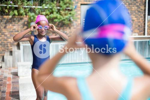 Girls wearing swimming goggles at poolside