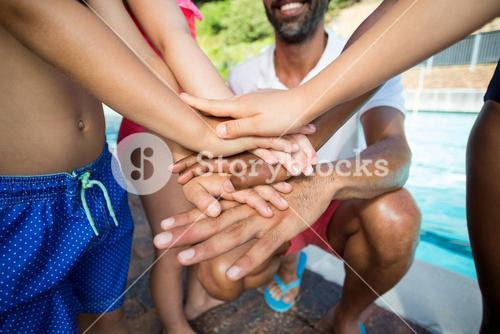 Male instructor and children stacking hands at poolside