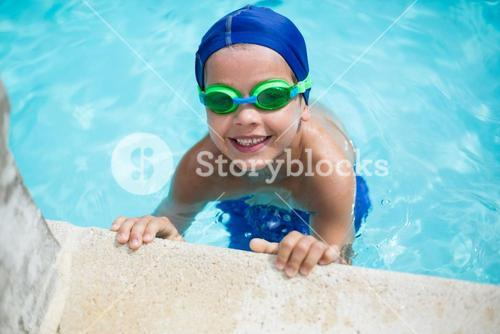 Little boy leaning at poolside