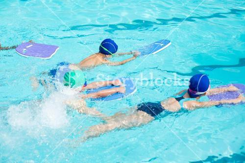 Little swimmers with kickboards swimming in pool
