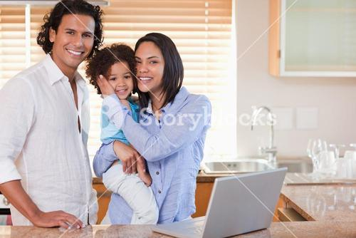 Family surfing the internet in the kitchen together