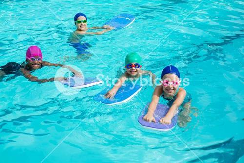 Little swimmers with kickboards enjoying in pool