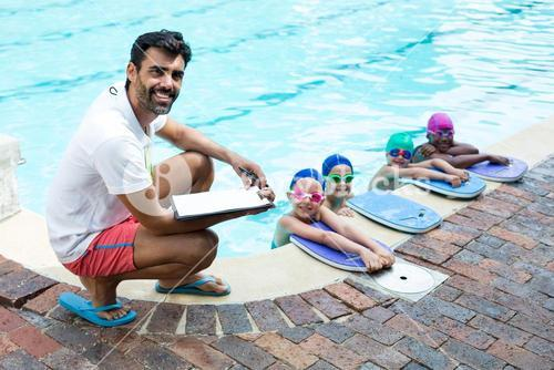 Male instructor with little swimmers at poolside