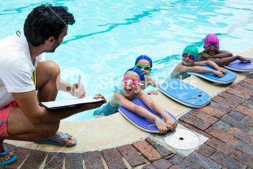Instructor writing on clipboard with swimmers at poolside