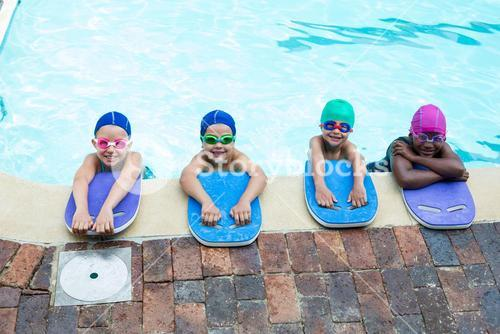 Little swimmers with kickboards at poolside
