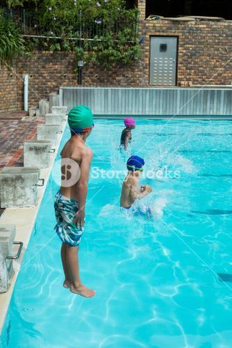 Swimmers jumping in swimming pool at leisure center