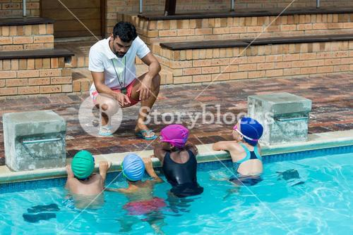 Instructor advising little swimmers at poolside