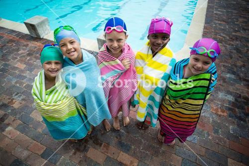 Swimmers wrapped in towels standing at poolside
