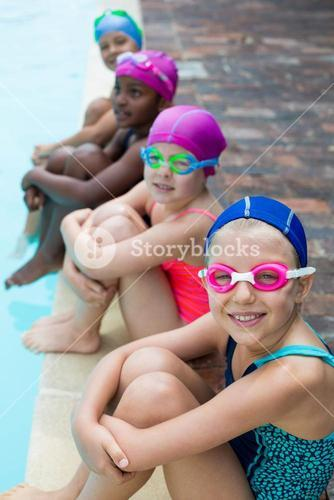 Little swimmers sitting at poolside