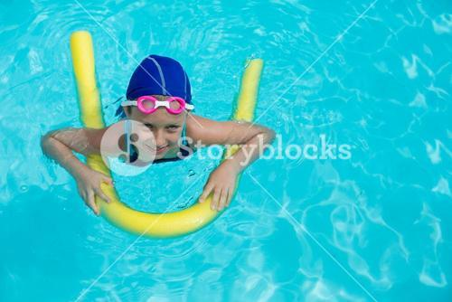 Little girl swimming with pool noodle