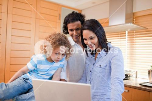 Happy family surfing the internet in the kitchen together