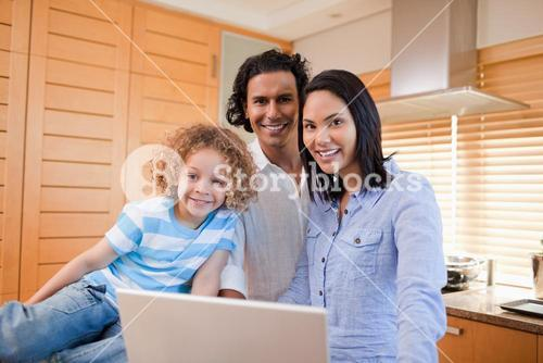 Cheerful family surfing the internet in the kitchen together