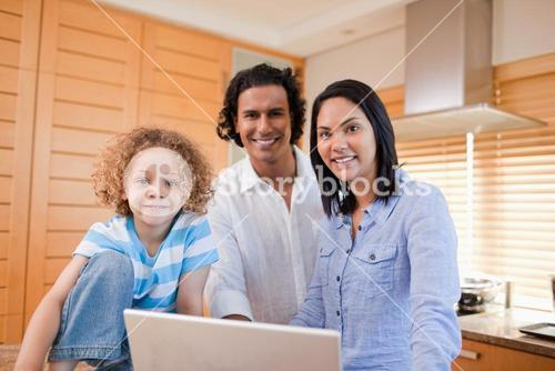 Joyful family surfing the internet in the kitchen together