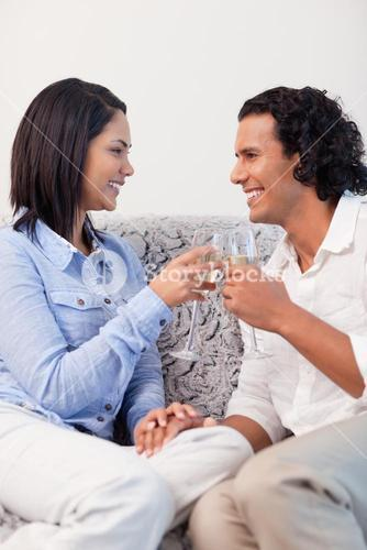 Couple drinking sparkling wine on the sofa