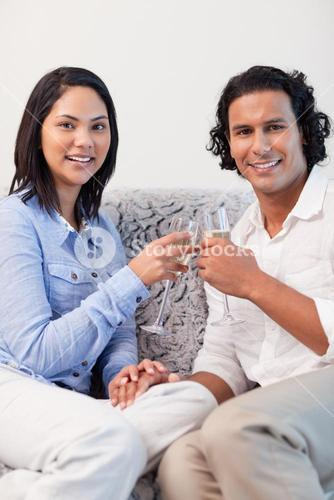 Couple drinking sparkling wine on the couch