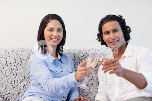 Couple celebrating with sparkling wine on the sofa