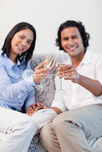 Couple celebrating with sparkling wine in the living room