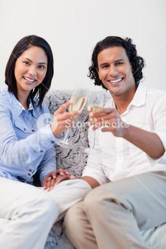 Happy couple drinking sparkling wine on the sofa