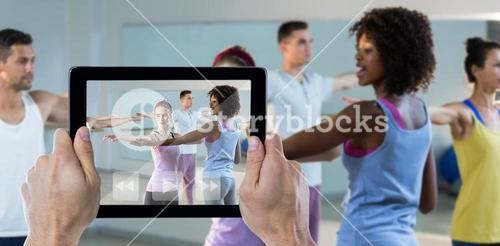 Composite image of cropped hand holding digital tablet
