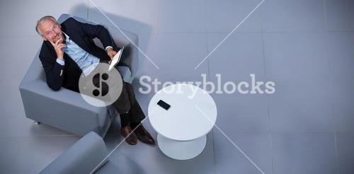 Businessman sitting on chair using digital tablet in office