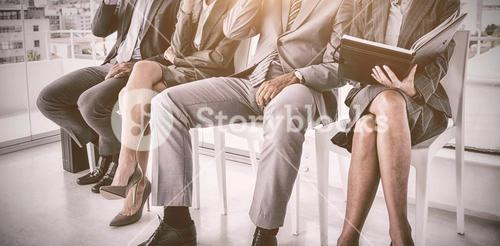Well dressed business people waiting to be called for interview