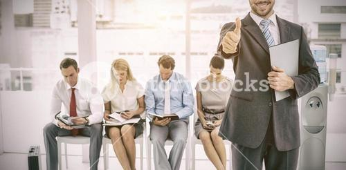 Businessman gesturing thumbs up against people waiting for interview